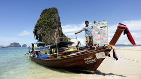 KRABI THAILAND-MAY 4 : Railay beach famous attractions. Unidentified man and longtail boat tune into restaurants and small shops for tourists on the beach. on Stock Photo