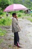 KRABI THAILAND - OKTOBER 28, 2013: Gammal asiatisk man under paraplyet i regn Arkivfoton