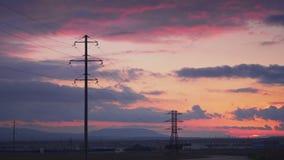Krachtcentrale met reusachtige elektrische steunen bij zonsondergang en een minibus met arbeiders stock video