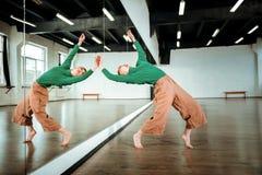Krachtige roodharige yogainstructeur met haarbroodje doen die dichtbij de spiegel overspannen stock foto's