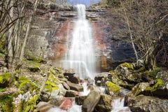 Krachtige, zonovergoten waterval die onderaan de rode klip stromen stock afbeelding