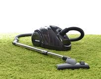 Krachtige zwarte stofzuiger op groene tapijtvloer Stock Fotografie