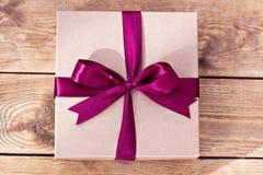 Kraft ask för gåvor som binds med en pilbåge på träbräden royaltyfri bild