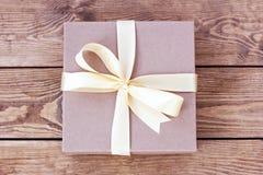 Kraft ask för gåvor som binds med en pilbåge på träbräden arkivbilder