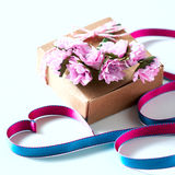 Kraft box and pink roses on white table, concept of Valentine`s Day, holiday. Selective focus. Red heart. Stock Images