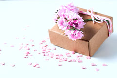 Kraft box and pink roses on white table, concept of Valentine`s Day, holiday. Selective focus. Red heart. Stock Image