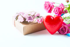 Kraft box and pink roses on white table, concept of Valentine`s Day, holiday. Selective focus. Red heart. Royalty Free Stock Photography