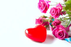 Kraft box and pink roses on white table, concept of Valentine`s Day, holiday. Selective focus. Red heart. Royalty Free Stock Photo