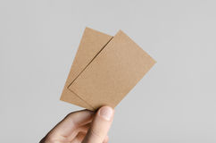 Kraft Business Card Mock-Up (85x55mm). Male hands holding kraft cards on a gray background Stock Photo