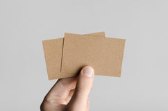 Kraft Business Card Mock-Up (85x55mm). Male hands holding kraft cards on a gray background Royalty Free Stock Image