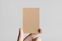 Kraft Business Card Mock-Up (85x55mm). Male hands holding kraft cards on a gray background Royalty Free Stock Photo
