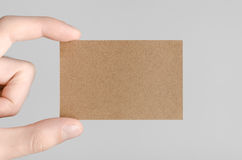 Kraft Business Card Mock-Up (85x55mm). Male hands holding kraft cards on a gray background Royalty Free Stock Photography