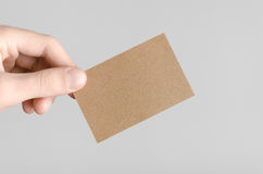 Kraft Business Card Mock-Up (85x55mm). Male hands holding kraft cards on a gray background Royalty Free Stock Images