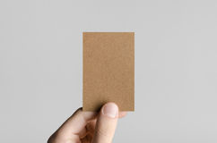 Kraft Business Card Mock-Up (85x55mm). Male hands holding kraft cards on a gray background Royalty Free Stock Photos