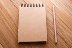 Kraft cover notebook on wood table. Spiral notebook with kraft cover and pencil on wood table Royalty Free Stock Images