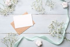 Kraft envelope with blank card for invitation or congratulation and bunches of flowers on light blue wooden background. Female wed stock image