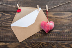 Kraft envelope, blank sheet of paper on rope with clothespins Royalty Free Stock Images