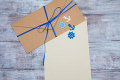 Kraft envelope with blue ribbon and blank sheet paper Stock Images