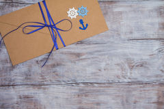 Kraft envelope in marine style with blue ribbon, anchor and steering wheel Royalty Free Stock Photos