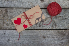 Kraft envelope, red hearts, scissors and twine on wooden background Stock Photo