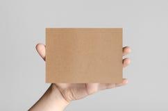 Kraft A6 Flyer / Postcard / Invitation Mock-Up. Male hands holding kraft flyers on a gray background Royalty Free Stock Image