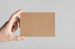 Kraft A6 Flyer / Postcard / Invitation Mock-Up. Male hands holding kraft flyers on a gray background Stock Image
