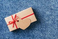 Kraft gåvaask med den röda pilbågen och etiketten royaltyfri fotografi