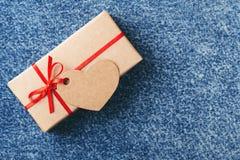 Kraft gåvaask med den röda pilbågen och etiketten arkivfoto