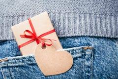 Kraft gåvaask med den röda pilbågen och etiketten fotografering för bildbyråer