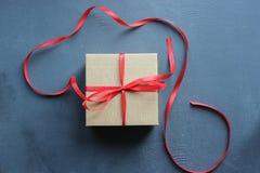 Kraft gåvaask med det röda bandet på texturerad svart tappningbakgrund royaltyfri bild