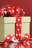 Kraft gift box with red polka dot ribbon Royalty Free Stock Photography