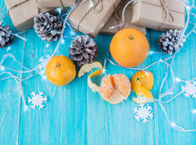 Kraft gift boxes, garland, candles, mandarins , snowflakes, Christmas decorations, cones on the wooden blue background Royalty Free Stock Photo