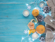 Kraft gift boxes, garland, candles, mandarins , snowflakes, Christmas decorations, cones on the wooden blue background Royalty Free Stock Image