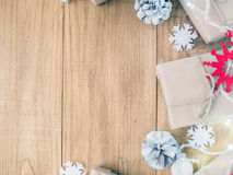Kraft gift boxes, garland, Christmas decorations, cones on the wooden background. Shallow Selective focus. Copyspace Stock Photo