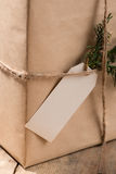 Kraft paper box and green leaves on woodean background. Royalty Free Stock Photos