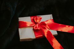 Kraft paper envelope tied with a red ribbon as a gift message. The gift is tied with a red bow against the background of royalty free stock images