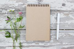 Kraft paper spiral notebook, white pen and summer flowers on rustic wooden background. Mock-up Royalty Free Stock Photography