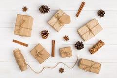 Kraft pappers- gåvor och kryddor på den vita tabellen Den original- dekoren för jul Den härliga orienteringen, den bästa sikten,  royaltyfri bild
