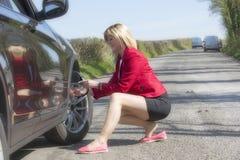Kraftfahrer, der Reifendruck eines Autos überprüft Lizenzfreie Stockfotos