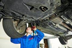 Kraftfahrzeugmechaniker, der Autosuspendierung in der Tankstelle kontrolliert Lizenzfreie Stockfotos