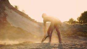 Kraftig crossfit som utbildar en man med en uppblåst torso i en buckla, slår repen kraftfullt på jordningen som lyfter damm arkivfilmer