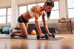 Kraftig kvinna som gör push-UPS på hantlar arkivfoto