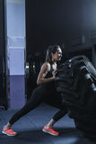 Kraftig muskulös kvinnaCrossFit instruktör som gör gummihjulgenomkörare på idrottshallen Royaltyfria Foton