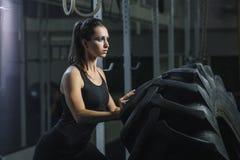 Kraftig muskulös kvinnaCrossFit instruktör som gör gummihjulgenomkörare på idrottshallen arkivbild
