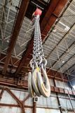 Kraftiga lastkrokar hänger på en lång påfyllningkedja Fotografering för Bildbyråer