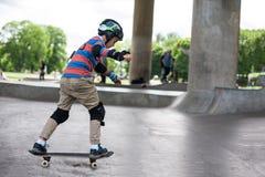 Kraftiga roliga unga grabbar utbildas i en skridsko parkerar Arkivfoton