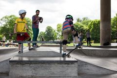 Kraftiga roliga unga grabbar utbildas i en skridsko parkerar Royaltyfria Bilder