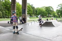 Kraftiga roliga unga grabbar utbildas i en skridsko parkerar Royaltyfri Bild