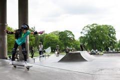 Kraftiga roliga unga grabbar utbildas i en skridsko parkerar Fotografering för Bildbyråer
