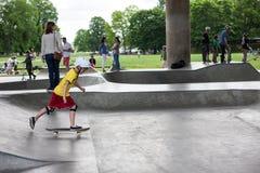 Kraftiga roliga unga grabbar utbildas i en skridsko parkerar Arkivfoto